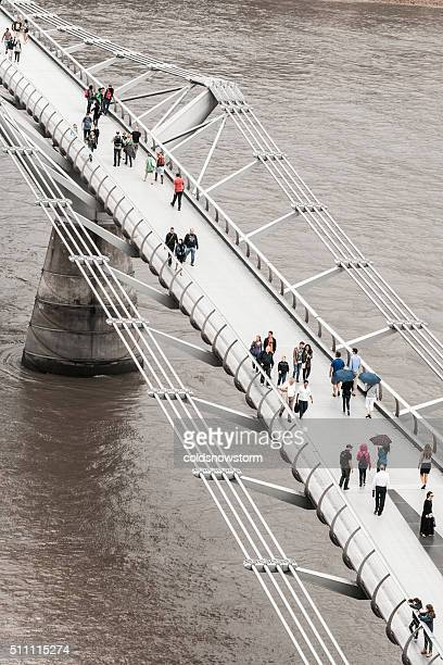 Tourists and Pedestrians walking across Millennium Bridge, London, UK