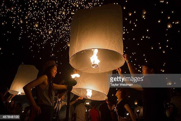 Tourists and Thai locals gather to release paper lanterns at the Lanna Dhutanka Temple on October 25 2014 in Chiang Mai Thailand The Lanna Kathina...