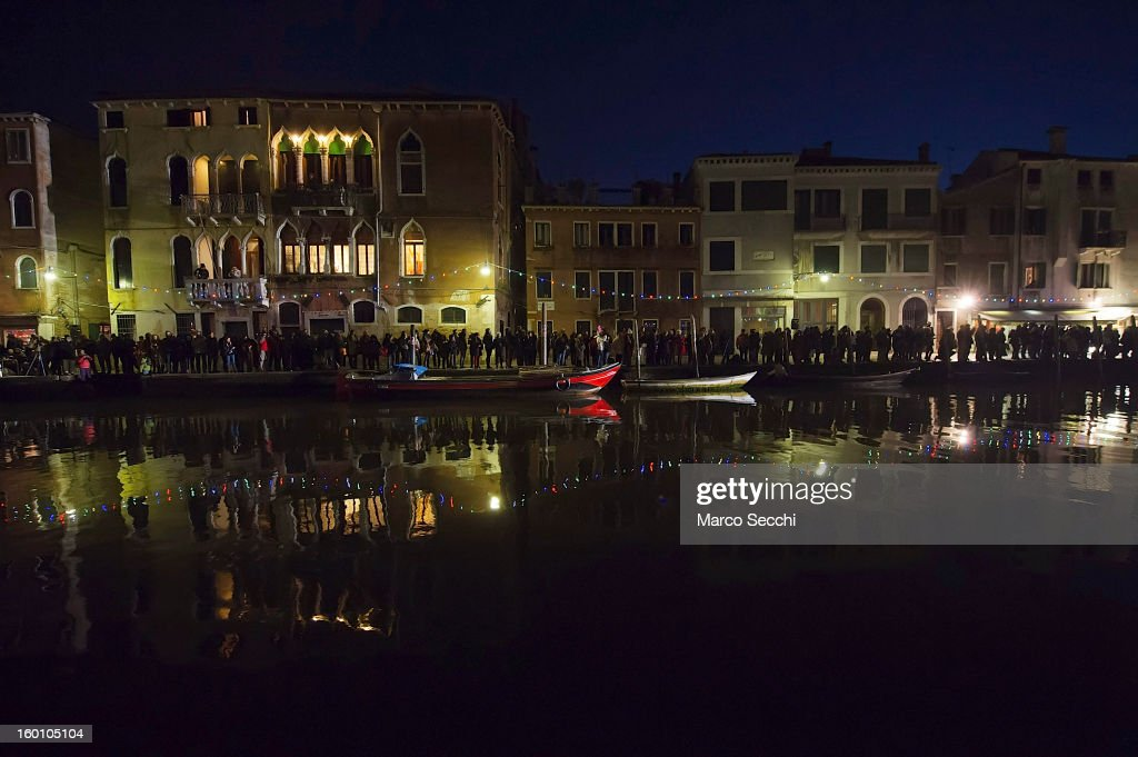 Tourists and Venetians wait on the banks of the Cannaregio Canal for the beginning of the water procession by French theatre company, Ilotopie, on January 26, 2013 in Venice, Italy. Today saw the opening of the Venetian Carnival, which runs till February 12th.