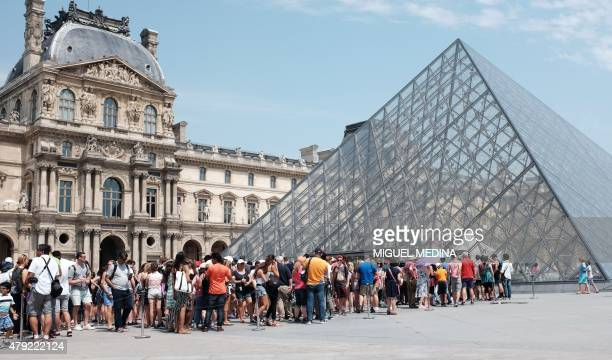 Tourists and visitors queue outside the Louvre Pyramid on a hot day in Paris on July 2 as a heatwave sweeps through Europe MEDINA
