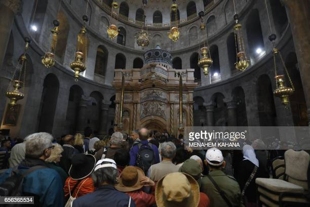 TOPSHOT Tourists and worshippers wait to access the newly restored shrine surrounding what is believed to be Jesus's tomb which was unveiled at a...