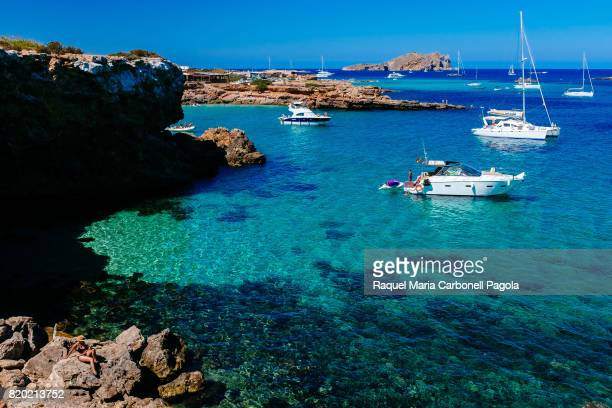 Tourists and yachts in Cala Comte beach