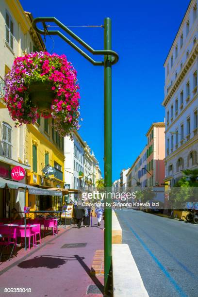 Tourists are passing by the restaurants and shops beside the road in Cannes, France.