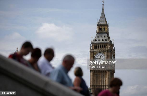 Tourists are pictured on Westminster Bridge beneath one of the four faces of the Great Clock of the Elizabeth Tower commonly referred to as Big Ben...