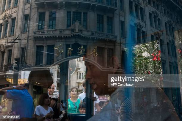 Tourists are seen in reflection walking on a street in Shanghai on August 14 2017 / AFP PHOTO / CHANDAN KHANNA