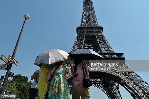 Tourists are seen protecting themselves from the sun with umbrellas at the Eiffel Tower during the heatwave on July 1 2015 in Paris France France is...