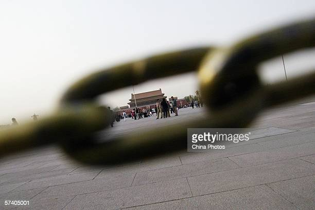 Tourists are seen through the chain links of a barrier at the Tiananmen Square on April 23 2006 in Beijing China Beijing tourist authorities are...