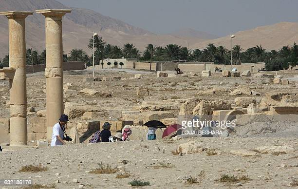 Tourists are seen visiting Palmyra also known as Tadmur in Arabic 220 kms northeast of the Syrian capital Damascus on June 19 a wealthy city located...