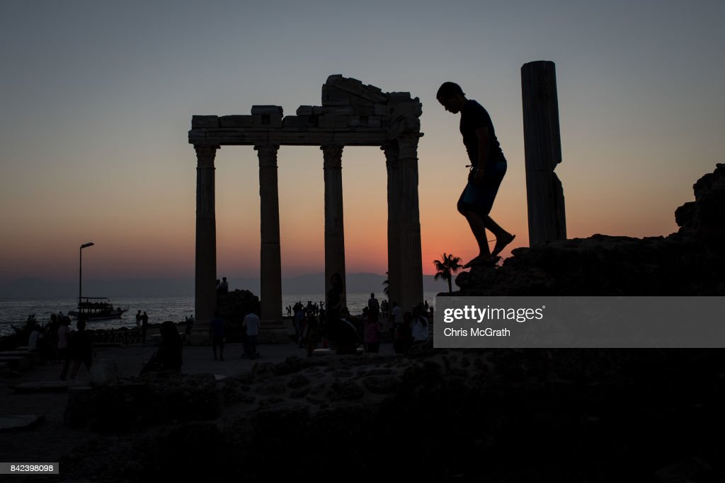 Tourists are seen visiting the Temple of Apollo on September 3, 2017 in Side, Turkey. Turkey's tourism industry spiraled into crisis in 2016 after a year of terrorist attacks, diplomatic rows and political uncertainty. Since then the tourism industry has struggled with foreign tourist numbers plummeting. However recent government figures for May 2017 show a 16 per cent rise in numbers on the previous year, bringing hope to local businesses and tour operators. Despite the return of Russian and European charter tour flights to Turkey and the overall increase in tourist numbers the industry is burdened with a 17bn debt, and with the current political crisis between Turkey and Germany continuing to deepen, recovery remains slow.