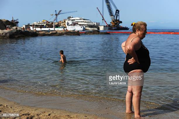 Tourists are seen while the last sponson is installed on the port side of the wrecked ship Costa Concordia on July 3 2014 in Isola del Giglio Italy A...