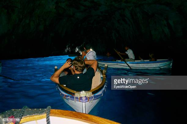 Tourists are sitting in rowing Boats and taking Pictures in the Cave of the Blue Grotto at the Island of Capri on June 24 2015 in Naples Italy