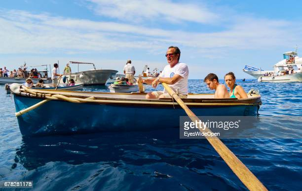 Tourists are sitting in small rowing boats to get into the Blue Grotto at the Island of Capri on June 24 2015 in Naples Italy