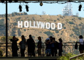 Tourists are slihouted against the distroted Hollywood sign from rising heat waves during a major heat wave in Southern California on June 28 2013 in...