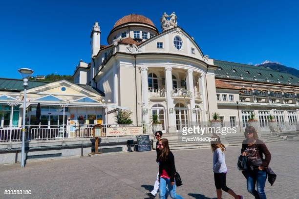 Tourists are walking next to the Kurhaus a famous Art Nouveau Building with the Restaurant Saxifraga in the city centre of Meran in South Tyrol on...