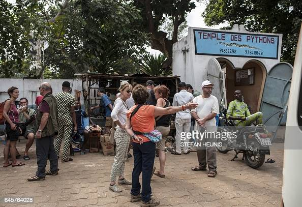 Tourists arrive to visit the Pythons Temple on January 11 2017 in the small coastal town of Ouidah some 40km from Benin's capital Cotonou With its...