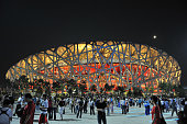 Tourists at Beijing National Stadium (birds nest), Olympic Park Square at night, Beijing, China