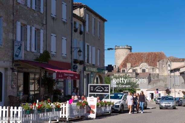 Tourists at cafe bar restaurant in ancient 13th Century bastide fortified town on September 20 2015 in Duras in Aquitaine France