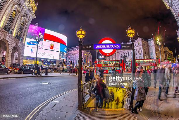 Tourists at Piccadilly Circus in London at night.