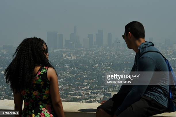 Tourists at the Griffith Observatory observation deck look out at the Los Angeles city skyline as heavy smog shrouds the city in California on May 31...