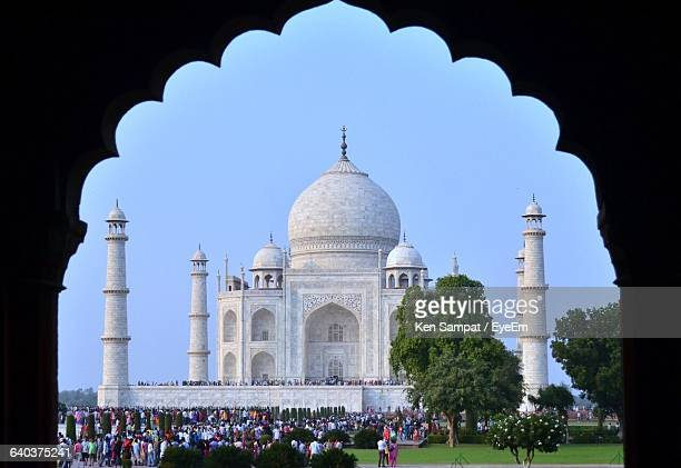 Tourists At The Taj Mahal Against Clear Sky Seen From Arch