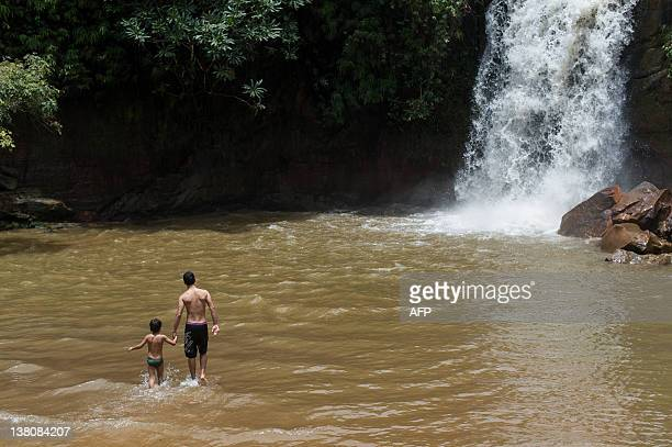 Tourists bath in the basin of the Veu de Noiva waterfall in the Chapada dos Guimaraes national park Mato Grosso state western Brazil on January 30...