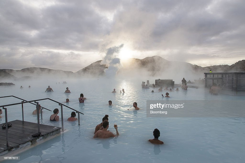 Tourists bathe in the Blue Lagoon geothermal spa as steam rises in Grindavik Iceland on Friday Nov 8 2013 Iceland is on schedule to release a...