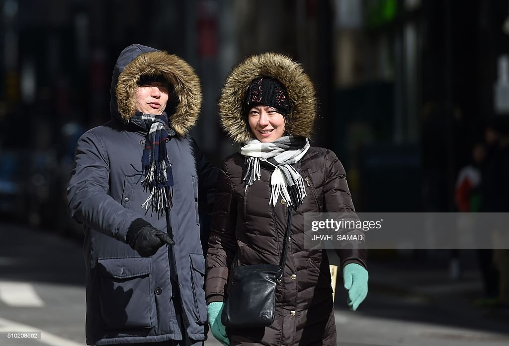 Tourists brave a cold morning to explore downtown Manhattan in New York, on February 14, 2016. / AFP / Jewel Samad