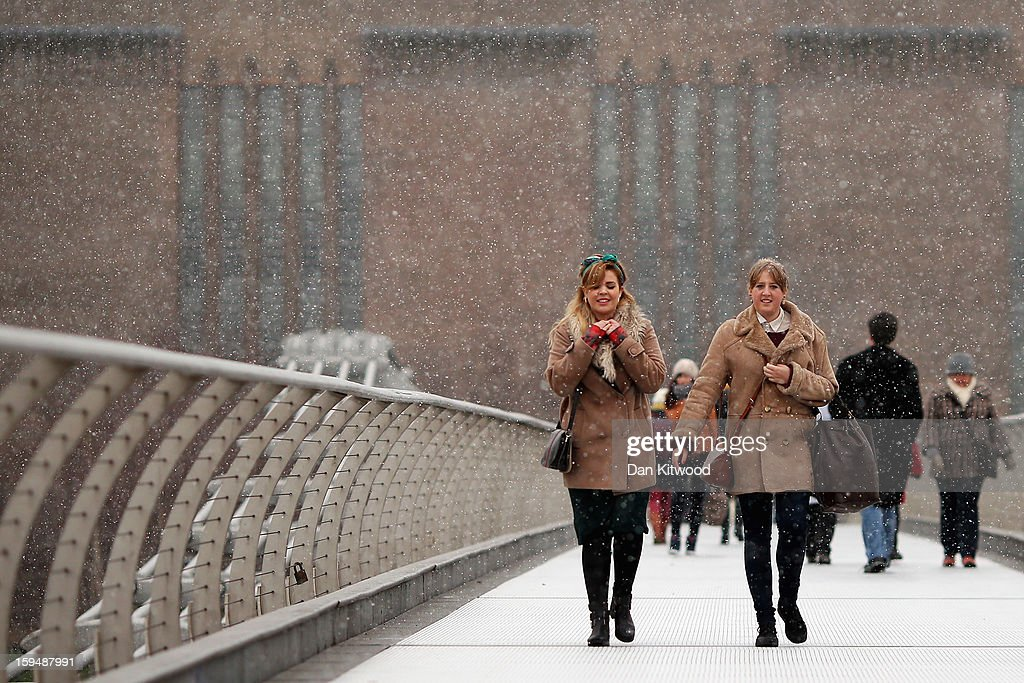 Tourists brave snow flurries as they cross Millenium Bridge on January 14, 2013 in London, England. Heavy snow is falling in parts of the United Kingdom.