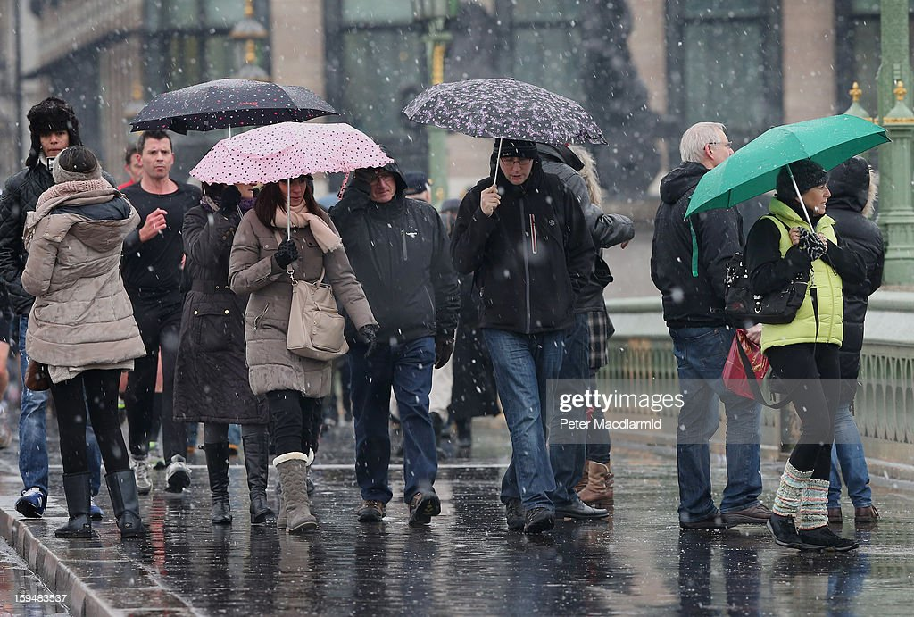 Tourists brave snow flurries as they cross Westminster Bridge on January 14, 2013 in London, England. Heavy snow is falling in parts of the United Kingdom.