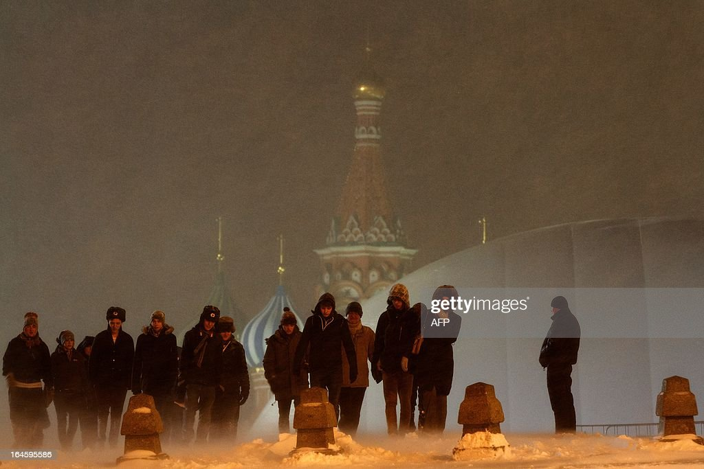 Tourists brave the snowstorm as they walk past a hardly seen huge temporary dome covering the mausoleum of Soviet state founder Vladimir Lenin (R) at the Red Square in Moscow, late on March 24, 2013. A snowstorm swept into Moscow yesterday as the temperatures in the Russian capital reached today -8 C (16 F), but due to high humidity and wind, weather experts said it would feel more like - 16 C (2 F). The snowfall that started yesterday was expected to continue into today, deluging the city with 28 to 35 centimeters of snow, the city media reported.