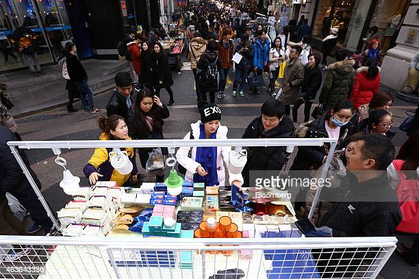 Tourists browse cosmetics at a street stall in the Myeongdong shopping district in Seoul South Korea on Sunday Feb 15 2015 South Korea kept its key...