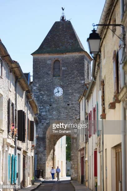Tourists by 13th Century medieval gateway clock tower in ancient bastide fortified town on September 20 2015 in Duras in Aquitaine France