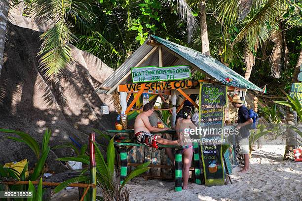 Tourists by beach shack at Source D Argent beach