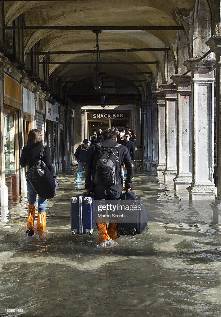 Tourists carry heavy luggage along Saint Mark's Square during today's Acqua Alta on November 5, 2013 in Venice, Italy. The high tide, or acqua alta as it is locally known, is a natural event most commonly affecting the city during Autumn and Winter.