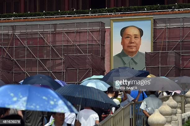 Tourists carry umbrellas to shelter from the heat as they walk towards the portrait of late communist leader Mao Zedong flanked by scaffolding on...