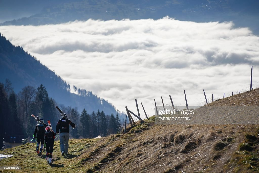 TOPSHOT Tourists carrying their skis walk on a snowless hill back to the resort of Leysin Swiss Alps on December 28 2015 In a season traditionally...