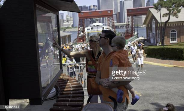 Tourists check a map after arriving by ferry boat July 17 2011 to Governors Island across New York Harbor at the tip of lower Manhattan Control of...