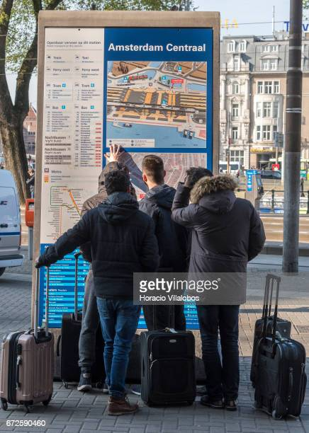 Tourists check a map outside the Central Station on April 20 2017 in Amsterdam Netherlands The city receives 85 million visitors who stay overnight...