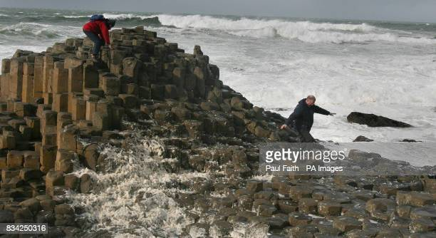 Tourists clamber over stones at the Giants Causeway during as storm batter Northern Ireland PRESS ASSOCIATION Picture date Wednesday March 12 2008...