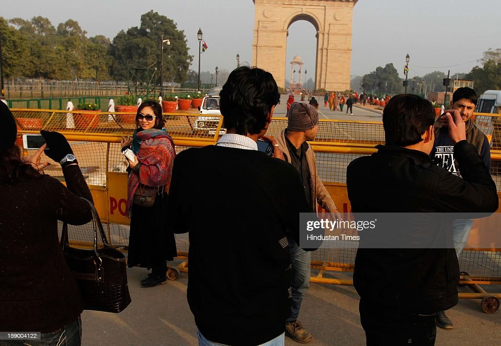 Tourists clicking the pictures of India Gate from behind the barricades on January 5, 2013 in New Delhi, India. Tourist were left disappointed as the India Gate was out of bound for them as CrPc Section 144 is still in place. The restriction were placed in many parts of central Delhi two weeks ago after series of protest against the rape of 23 year old girl in moving bus.