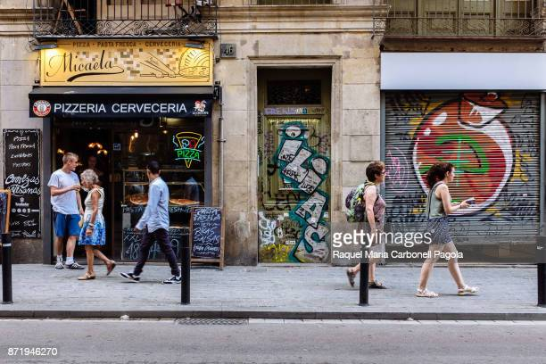 Tourists coming out of an italian pizza restaurant next to graffiti painted doorways