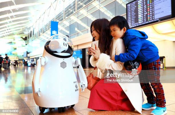 Tourists communicate with guidance robot 'Kaiba' at the Terminal 2 of Haneda Airport as the demostration trial continues on February 1 2017 in Tokyo...