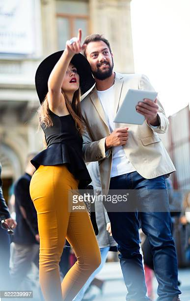 tourists couple holding a tablet and sightseeing
