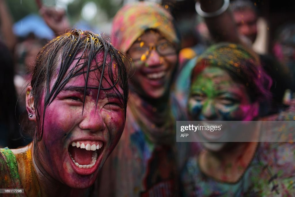 Tourists covered with coloured powder join the celebrations to mark 'Holi' at a temple in Kuala Lumpur on March 31, 2013. Holi, the festival of colours where people smear each other with coloured powder and water, is celebrated by Hindus across the country. AFP PHOTO / MOHD RASFAN