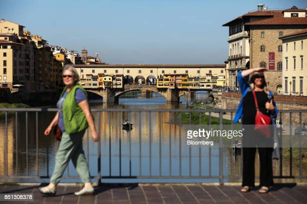 Tourists cross a bridge against a backdrop of the Ponte Vecchio bridge in Florence Italy on Friday Sept 22 2017 UK Prime Minister Theresa May will...