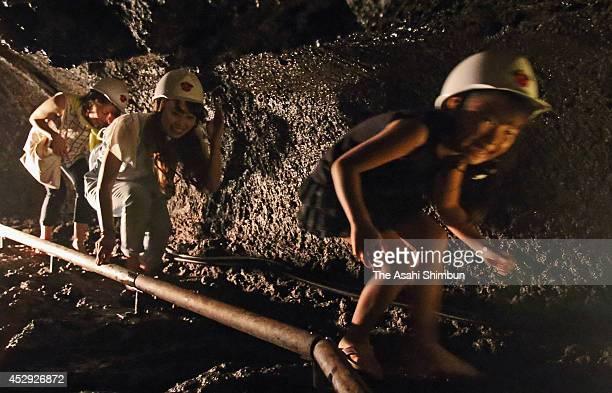 Tourists crouch as they explore the lava cave called 'Saiko Komori Ana' on July 26 2014 in Fujikawaguchiko Yamanashi Japan The temperature of the...