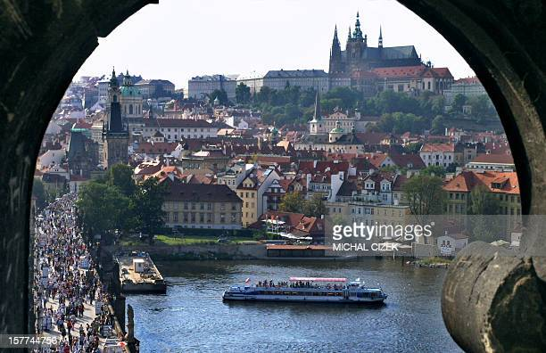 Tourists crowd in the middle of Charles Bridge in Prague 19 August 2005 Charles Bridge is a stone Gothic bridge that connects the Old Town quater and...