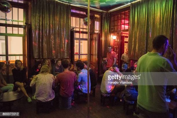 Tourists crowd the pole dancing lounge of 'Pensao Amor' a former brothel turned into a trendy bar in Pink Street Cais do Sodre neighborhood on...