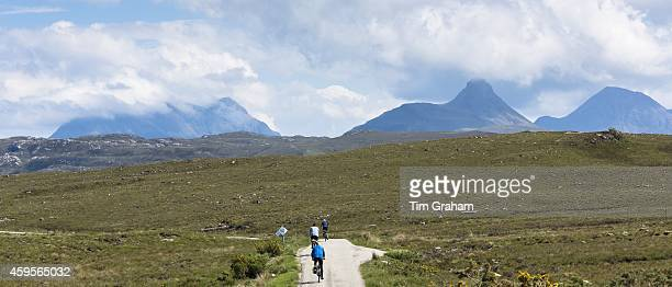 Tourists cycling by Stac Pollaidh Stack Polly in glacier mountain range in the North West Highlands Geopark in Coigach region of Scottish Highlands