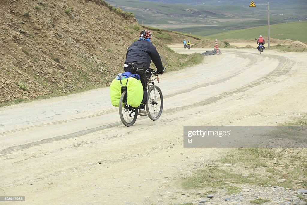 tourists cycling on mountain road to tibet,china : Stock Photo